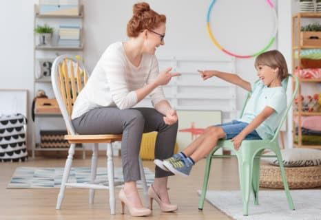 therapist and little boy pointing to each other