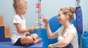 therapist and little girl playing together